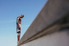 Shirtless young man standing on a wall Stock Images