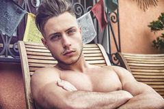 Shirtless Young Man Sunbathing in Lounge Chair Royalty Free Stock Photos