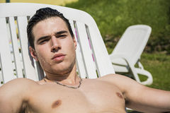Shirtless Young Man Sunbathing in Lounge Chair on Stock Photos