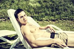 Shirtless Young Man Sunbathing in Lounge Chair on Royalty Free Stock Photo