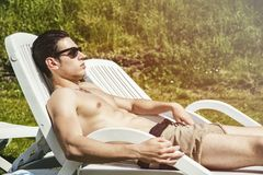 Shirtless Young Man Sunbathing in Lounge Chair on Stock Photo