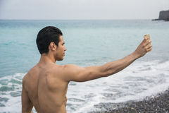Shirtless Young Man Taking Selfie Photos at Beach Royalty Free Stock Photography