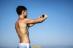 Shirtless Young Man Taking Selfie Photos at the Royalty Free Stock Photos
