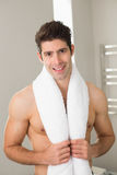 Shirtless young man with towel around neck. Portrait of a shirtless young man with towel around neck at home Royalty Free Stock Photo