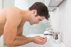 Shirtless young man washing face in bathroom Stock Photo