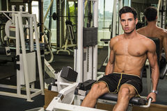 Shirtless young man working out on gym equipment Stock Photo