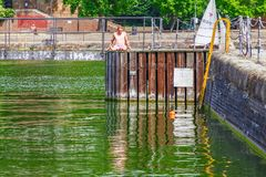 A shirtless young men sunbathe on the swimming dock at Shadwell. London, UK - June 21, 2017 - a shirtless young men sunbathe on the swimming dock at Shadwell Royalty Free Stock Image