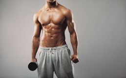 Shirtless young muscular man with dumbbell stock photo
