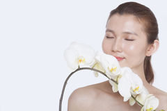 Shirtless young woman with eyes closed smelling a bunch of beautiful white flowers, studio shot stock image