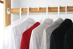 Shirts in closet. Shirts of different colors in the closet royalty free stock image