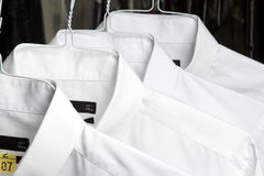 Shirts at the dry cleaners freshly ironed. Las camisas estan en perchas Stock Photos