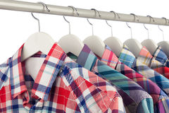 Shirts on hangers. Mens colorful checked shirts on white hangers, close-up, shallow dof, white background Royalty Free Stock Photos