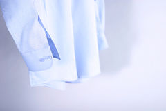 Shirts hanging. Light blue shirts hanging with shadow Royalty Free Stock Image