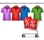 Shirts hanging on a bar and a shopping cart. Royalty Free Stock Photos