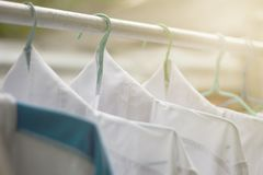 Shirts hanging on on open rail or clothes outdoors on laundry day. stock image