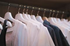 Shirts hanging on rack in wardrobe. Selective focus Royalty Free Stock Photos