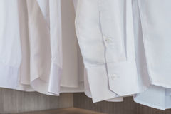 Shirts hanging on rack with white buttons Royalty Free Stock Photo