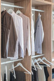 Shirts and pants hanging in wooden wardrobe. In modern closet Stock Photography