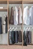 Shirts and pants hanging in wooden wardrobe Royalty Free Stock Images