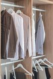 Shirts and pants hanging in wooden wardrobe Stock Image