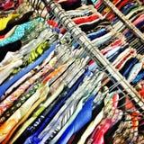 Shirts on the racks. Rows of colorful shirts hanging on the racks stock photography