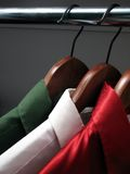 Shirts representing Italian flag. Colors of Italy: green, white and red shirts on wooden hangers in a closet royalty free stock photo