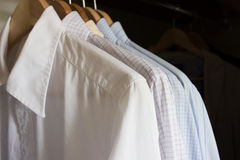 Shirts in a wardrobe. Several male shirts in light colors on wooden hangers in wardrobe Royalty Free Stock Photo
