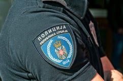 Shirtsleeve med emblemet av den serbiska polisen Översättning - polisen, republik av Serbien arkivbild