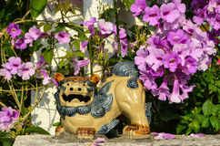 Shisa figure and pink flowers Royalty Free Stock Image