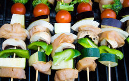 Shish-kabobs on a barbeque. Delicious tomato, onion, chicken, zucchini, mushroom, and broccoli shish-kabobs cook over a barbecue Stock Images