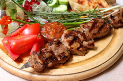 Shish kebab. On a wooden support with vegetables and spices Royalty Free Stock Image