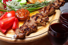 Shish kebab. On a wooden support with vegetables and spices Royalty Free Stock Photos