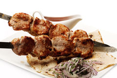 Shish kebab. Fried shish kebab on the plate with onion and sauce Royalty Free Stock Photos