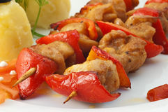Shish kebab. With tomatoes and a potato on a white dish close up Stock Images