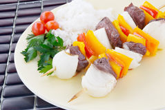 Shish kebab. Grilled shish kebab made with sirloin steak, bell peppers and vidalia sweet onions served with rice and tomatoes. Italian Parsley garnish Royalty Free Stock Photos