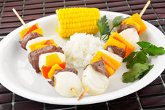 Shish kebab dinner. Grilled shish kebab made with sirloin steak and bell peppers. Served with rice and corn on the cob Stock Photo