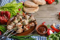 Shish Kebab From Pork On Skewers Laid Out On A Dish. Meat Cooked On An Open Fire. Still Life On A Wooden Background With Textiles. Stock Photography
