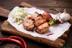 Shish kebab with marinated onions garnishing. Grilled pork meat with  marinated onions garnishing on wooden board. Summer delicious food, weekend bbq party stock images