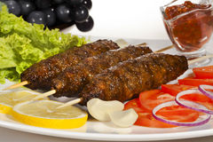 Shish-kebab. Meat on a skewer of lamb. Grilled Lamb Skewers with Vegetables and Sauce Stock Images