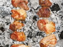 Shish kebab on metal skewers over charcoal with ash Royalty Free Stock Image