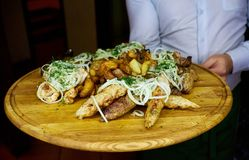 Shish kebab with onions on a wooden tray royalty free stock photography