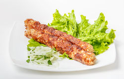 Shish kebab on a plate. With greens, onions Stock Photo