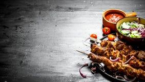 Shish kebab of pork and salad. Stock Photography