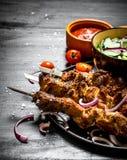 Shish kebab of pork and salad. Royalty Free Stock Photos