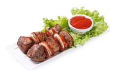 Shish kebab from pork with vegetables and sauce isolated Royalty Free Stock Photography
