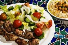 Shish kebab with a salad of fresh vegetables and hummus. Stock Photos