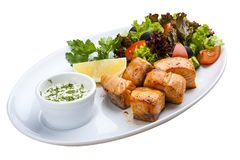 Shish kebab from salmon with vegetables and salad. On a white plate stock photography