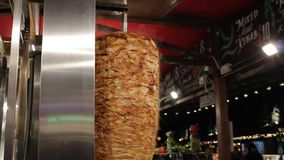 Shish kebab on skewer turning on spit while cooking Turkish traditional food