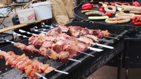 And shish kebab on skewers near.Street Food, Fast Food, Snack on the street, taseful, delicious. A huge grill on which aesthetically laid out roasted sausages stock footage