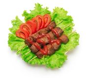 Shish kebab, tomato and green salad on white background. royalty free stock image